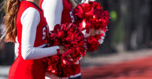 Cheerleaders in red and white holding pom poms.