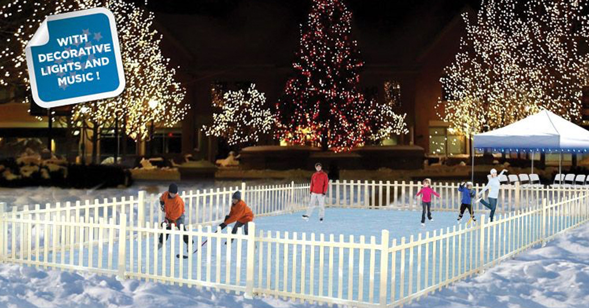 Children using a synthetic ice rink with lit up holiday trees in the background.